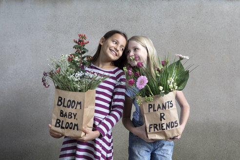 Portrait of two smiling girls holding paper bags with flowers - PSTF00194