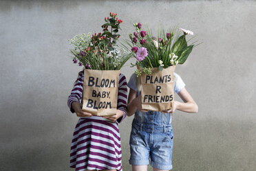 Two girls standing side by side hiding behind paper bags with flowers - PSTF00197