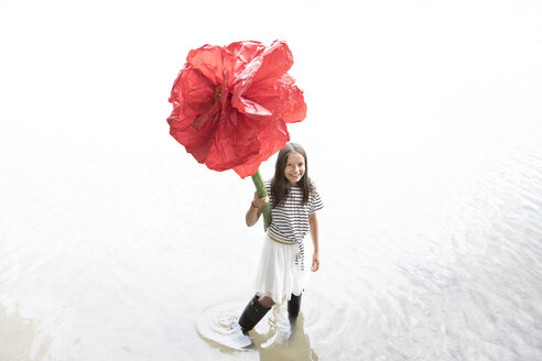 Portrait of smiling girl standing in a lake holding oversized red artificial flower - PSTF00203