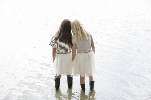 Back view of two best friends standing head to head in a lake - PSTF00206