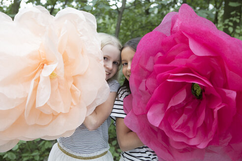 Two smiling girls with two oversized artificial flowers - PSTF00209
