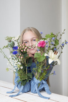 Portrait of smiling blond girl with bunches of flowers in sleeves of her dress - PSTF00215