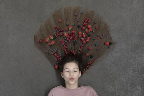 Portrait of girl lying on floor with eyes closed and fruits on hair - PSTF00218