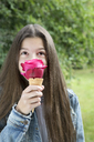 Girl smelling pink rose blossom in ice cream cone - PSTF00224
