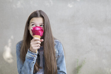 Girl smelling pink rose blossom in ice cream cone with - PSTF00227