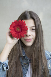 Portrait of smiling girl with flower head of red Gerbera - PSTF00233