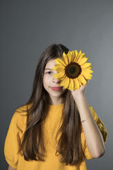 Portrait of smiling girl with sunflower in front of grey background - PSTF00239