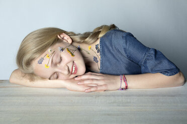 Portrait of smiling blond girl with tattoo of pressed flowers on her face - PSTF00242