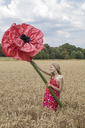 Smiling girl standing on a field with oversized red artificial flower - PSTF00251