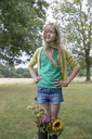 Portrait of blond girl standing on a meadow with bunches of flowers in her rubber boots - PSTF00254