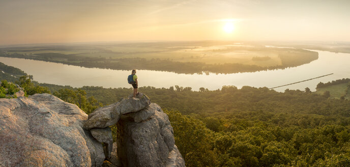 Woman standing on sandstone overhang watching sunrise from summitofPetitJean Mountainabove Arkansas River Valley - AURF05767