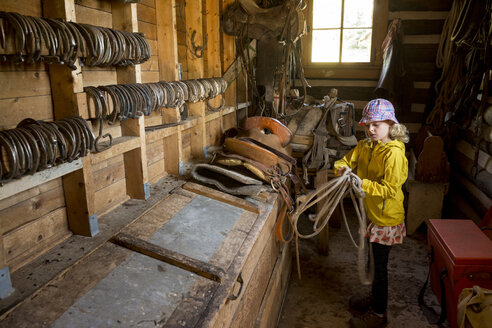 Young girl coiling rope in tack room while getting ready for horseback ride - AURF05770