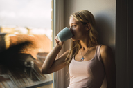 Blond young woman drinking coffee from mug looking out of window - KKAF01983