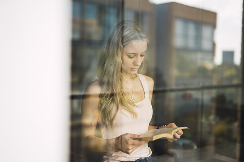 Young woman reading a book behind windowpane - KKAF01989