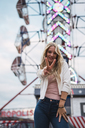 Portrait of smiling young woman on a funfair - KKAF02013
