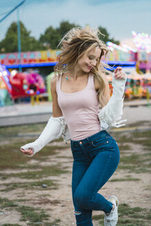 Happy young woman moving on a funfair - KKAF02022