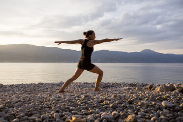 Young woman doing yoga at the stony beach in the evening, Warrior pose - JESF00174