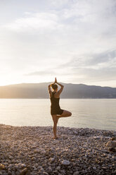 Young woman doing yoga on a stony beach at sunset, tree position - JESF00177