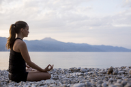 Young woman doing yoga at the stony beach in the evening, meditation - JESF00180