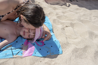 Mother kissing daughter lying on beach towel on the beach - PSIF00089