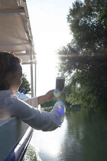 Woman on a boat trip taking cell phone picture - PSIF00098