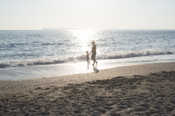 Greece, Parga, mother and daughter walking on the beach at sunset - PSIF00101