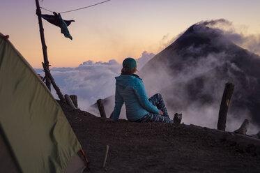 Female hiker looking at view at summit of Acatenango Volcano, Guatemala - AURF06063