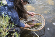 Angler holding caught brown trout (Salmo trutta), Colorado, USA - AURF06069