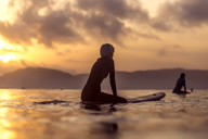 Female surfer in sea at sunset - AURF06075