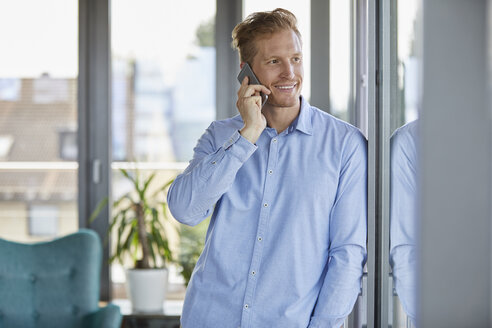 Smiling businessman on the phone at the window - RBF06791
