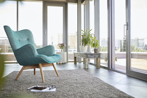 Home interior with armchair, tablet and view on roof terrace - RBF06815