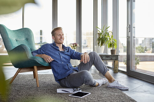 Smiling young man sitting on carpet with tablet and notepads at home - RBF06818