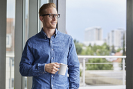 Smiling young man with cup of coffee standing at balcony door - RBF06842