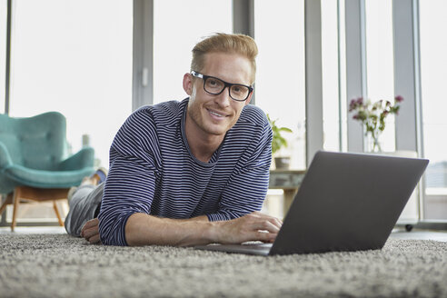 Portrait of smiling young man lying on carpet at home using laptop - RBF06848