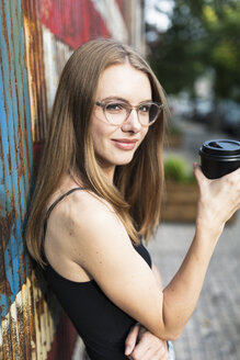 Young woman holding cup of coffee, standing in front of metal fence with stars and stripes - GIOF04501