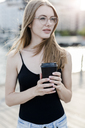 Young woman holding cup of coffee - GIOF04513