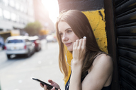 Young woman leaning on street corner, listening music, using smartphone - GIOF04516