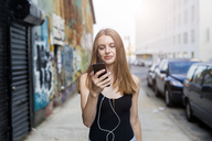 Young woman walking in street, listening music, using smartphone - GIOF04522
