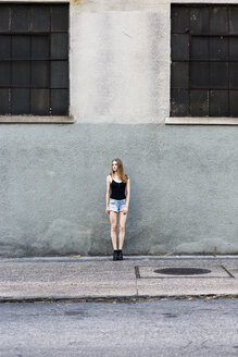 Young woman standing in front of building, waiting - GIOF04528