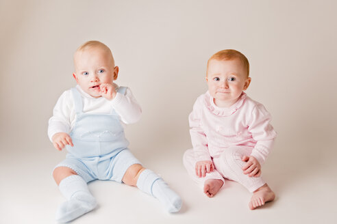 Portrait of baby boy and baby girl sitting side by side - NMS00254