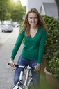 Young woman with bicycle in the city - PNEF00972