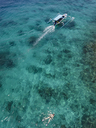 Indonesia, Bali, Aerial view of Blue Lagoon, snorkeler and banca boat - KNTF01809
