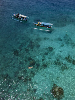 Indonesia, Bali, Aerial view of Blue Lagoon, snorkeler and banca boats - KNTF01812