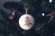 Christmas bauble hanging at Christmas tree - MOMF00498