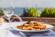 Italy, Atrani, plate of Penne Rigate with tomato sauce and tuna - FLMF00078