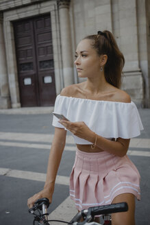 Fashionable young woman exploring Barcelona with a bicycle, using smartphone - AFVF01590