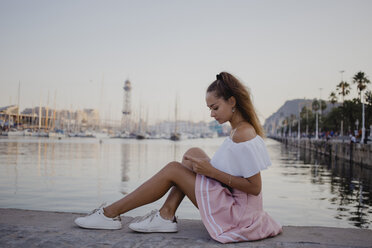 Fashionalble young woman sitting at the harbour of Barcelona, using smartphone - AFVF01608