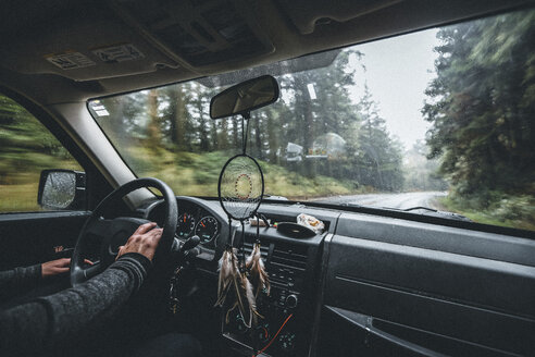 Cropped hands of man driving car on road amidst forest - CAVF48767