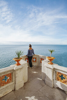 Rear view of young woman looking at sea while standing on building terrace against sky - CAVF48770
