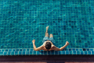 High angle view of shirtless man relaxing while sitting in pool at tourist resort - CAVF48773